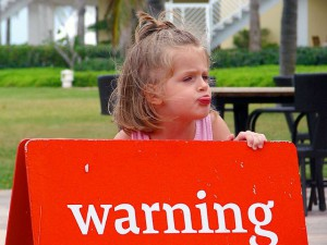Child holding a warning sign